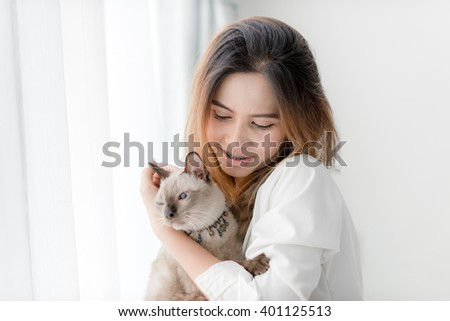 beautiful smiling Asian girl holding her cat with window light at home.