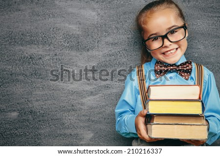 Beautiful smiling girl against chalkboard. School concept