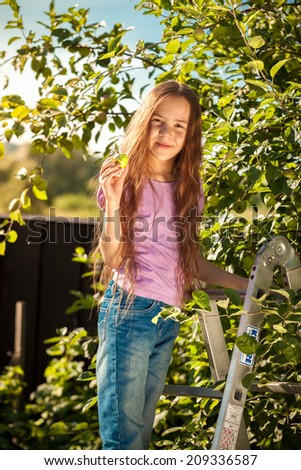 Beautiful smiling girl standing on ladder at garden