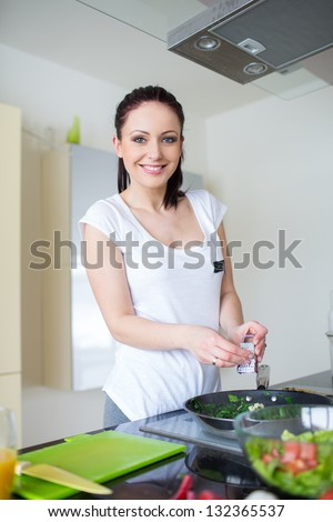 Beautiful smiling woman preparing fresh meal