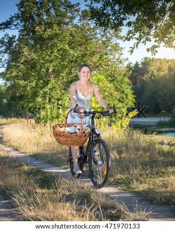 Beautiful smiling woman riding bicycle by the river at sunny day