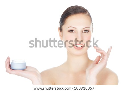 Beautiful smiling young woman applying moisturizing creme over white background