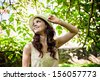 Beautiful smiling young woman wearing straw hat outdoors - stock photo
