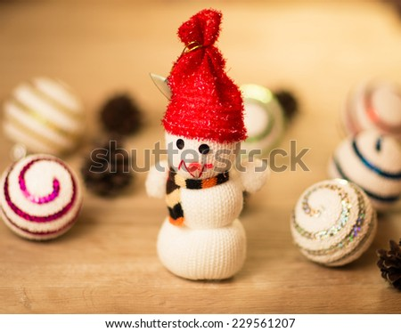 beautiful snowman with Christmas balls and beautiful lighting on wooden background