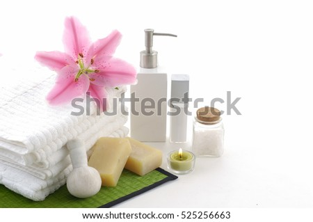 Beautiful spa composition with lily flowers, towels, soap, bath salt and candles