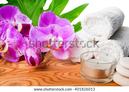 beautiful spa still life with blooming lilac orchid, white stones, towels, candle and tropical green leaf on root wood background is isolated, close up