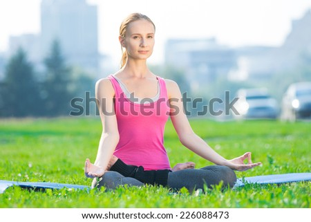 Beautiful sport woman doing stretching fitness exercise in city park at green grass. Yoga lotus pose