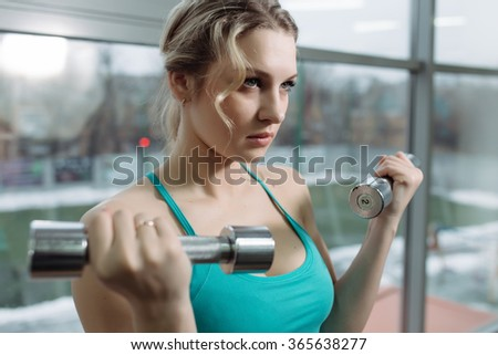 Beautiful sportswoman doing exercise for biceps with dumbbell in gym