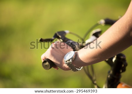 Beautiful sporty young woman hand griping bicycle handle in bright sunlight on summer day, close up
