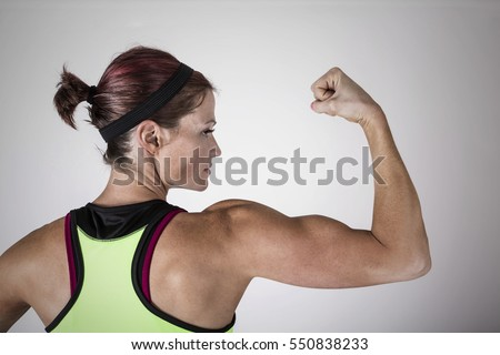 Beautiful strong muscular woman flexing her biceps and arm muscles. View from behind to show her ripped back and arms.Female Body Builder