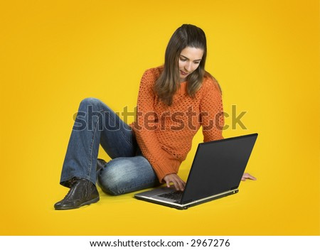 Beautiful student woman with a laptop over a yellow background