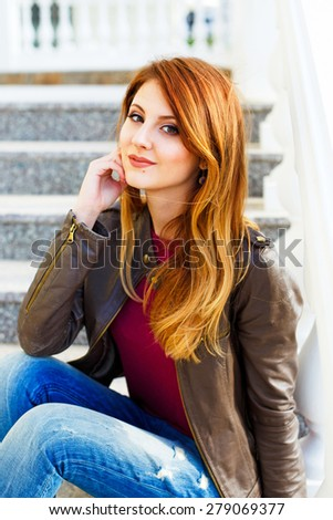 Beautiful stylish girl in jeans and a leather jacket sitting on the stairs