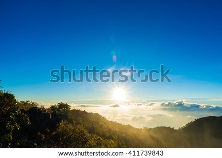 Beautiful summer sunrise on the top of mountain with Rays of Light, fog and cloud mountain