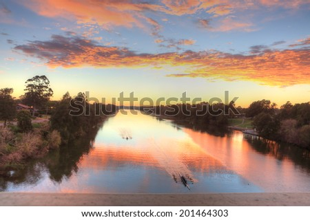 Beautiful sunrise over the Nepean River, Penrith NSW, Australia. Kayakers practice early morning before larger watercraft stir up the waters