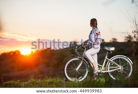 Beautiful sunset and girl in Ukrainian embroidery with retro bike enjoying them. Blurred background