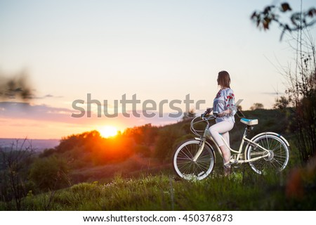 Beautiful sunset and sporty woman with bicycle enjoying them. Blurred background