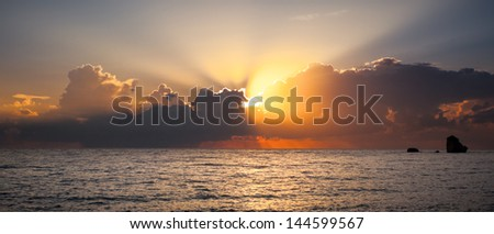 Beautiful Sunset Over Sea Horizon With Stripes From Sun Through Clouds in Cyprus
