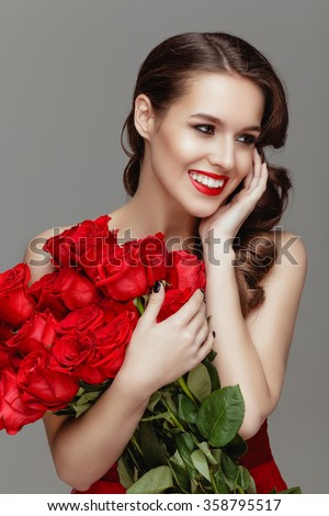 Beautiful  surprised woman  with red lips posing with flowers  in the studio on a grey background.