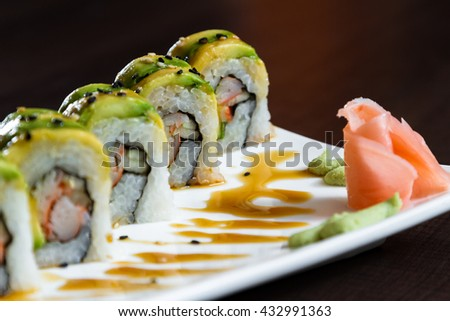 beautiful sushi roll topped with avocado stuffed with crab meat garnished with a sweet sauce and sesame seeds