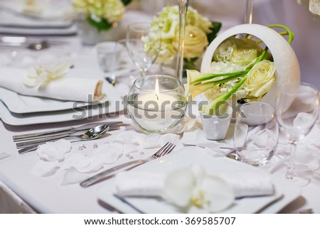 Beautiful table set with flowers and candles for an event party or wedding reception