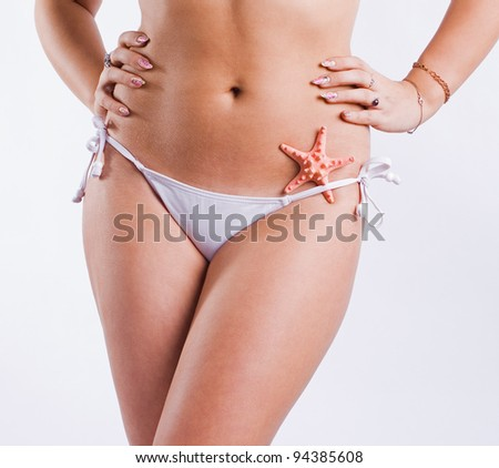 Beautiful tanned body of a young woman on a white background.