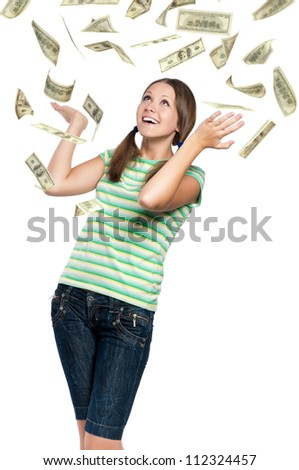 Beautiful teen girl catching falling dollars banknotes on white background