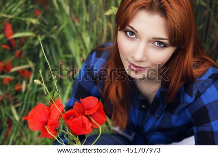 Beautiful teenage girl with red hair dressed in blue shirt holds bunch of poppies. Shallow depth of the field, focus on eyes