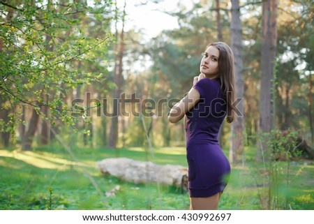 Beautiful Teenage Model girl Dressed in Casual Short Dress on the park.