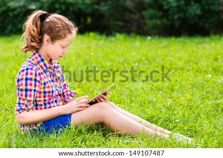 Beautiful teenager girl in casual clothes sitting on the grass with digital tablet on her knees, reading and surfing, outdoor portrait