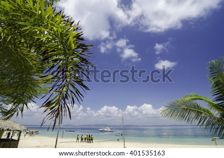beautiful tropical island with white sandy beaches, crystal blue sea water and cloudy blue sky at sunny day. crop image of palm tree and group of tourists