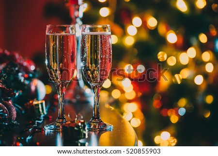 Beautiful two glasses of champagne standing on the table in the background of a blurred room with a decorated Christmas tree and fireplace. Soft focus. Shallow DOF