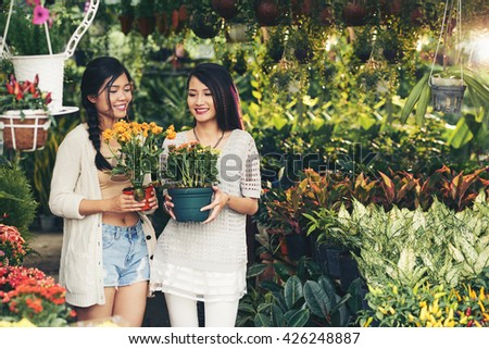 Beautiful Vietnamese girls holding pots with bright blooming flowers
