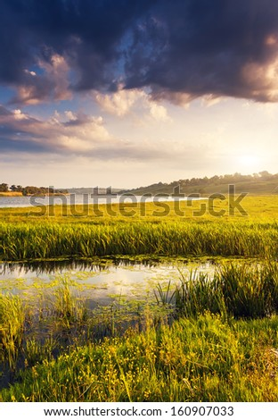 Beautiful view of sinuous river in summer. Dramatic overcast sky. Southern Buh River, Ukraine, Europe. Beauty world.