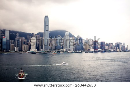 Beautiful view on Hong Kong harbour with cloudy sky and city buildings on background