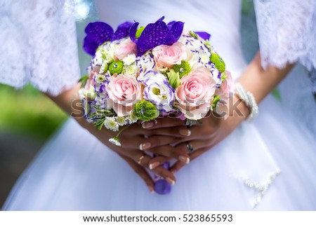 Beautiful wedding bouquet in hands of a young bride with a beautiful wedding manicure on nails.