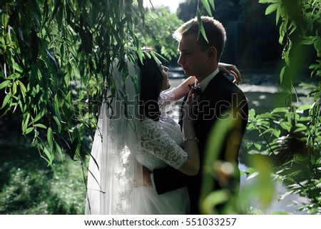 Beautiful wedding couple hugging in the park at the camera, close view