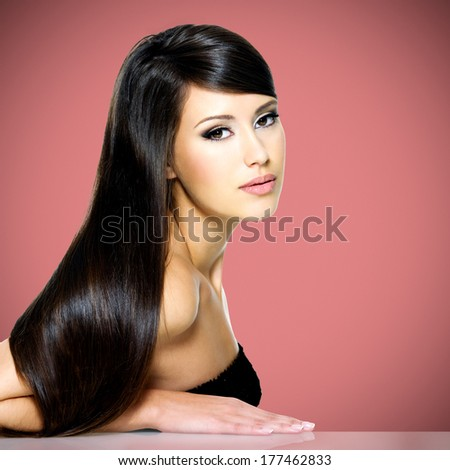 Beautiful white woman with long brown hair posing at studio