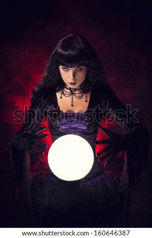 Beautiful witch or fortune teller with a crystal ball, studio shot over smoky background