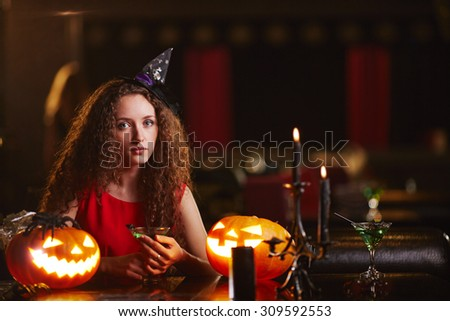 Beautiful witch with martini looking at camera