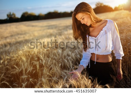 Beautiful woman and golden barley fields