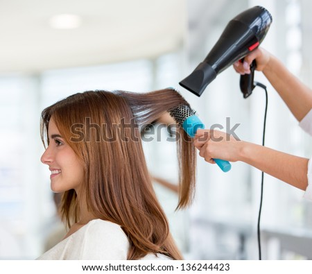 Beautiful woman at the hairdresser blow drying her hair