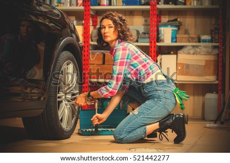 beautiful woman auto mechanic in blue overalls checks a socket wrench car tire. instagram image filter retro style