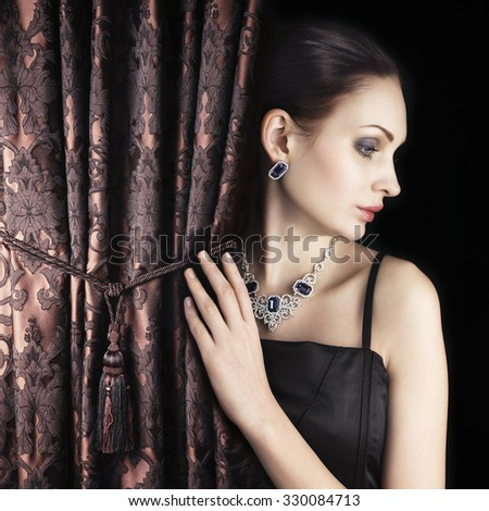 Beautiful woman behind satin embroidered curtain with lace pattern