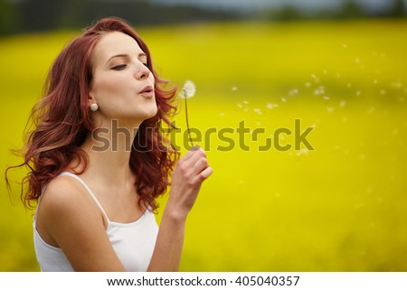 beautiful woman blowing dandelion in the field