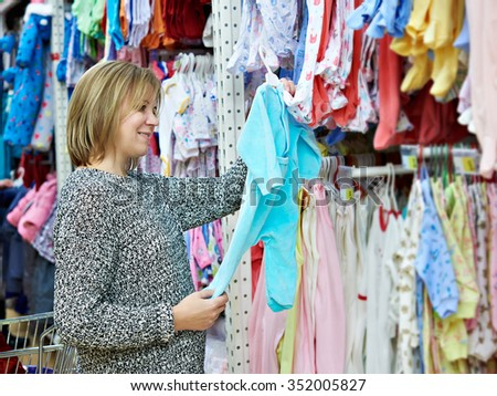 Beautiful woman chooses child rompers in store