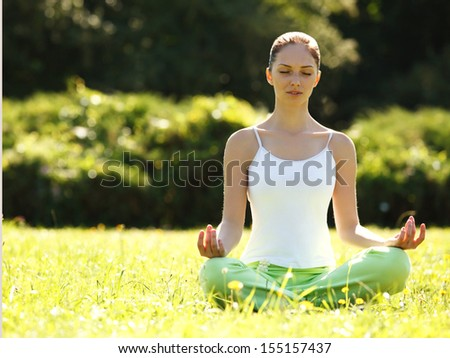 Beautiful Woman doing Yoga Exercises in the Park.