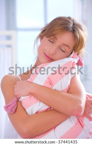 Beautiful woman embracing pillow on bed and dreaming about something