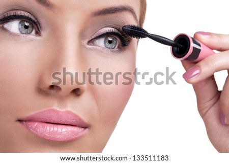 Beautiful woman face with mascara brush