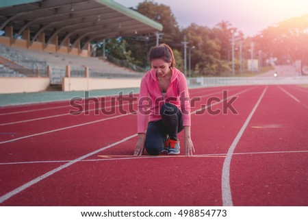 Beautiful woman fitness runner stretching and preparing to run.woman worm up body with sunset background.