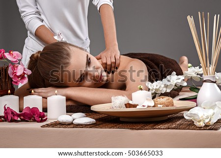 Beautiful woman having a wellness back massage at spa salon. The girl relaxes in the spa salon. empty space for your ad text.